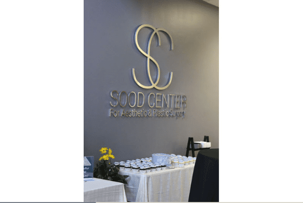 Sood Center Logo on Wall with Food Table Beneath it