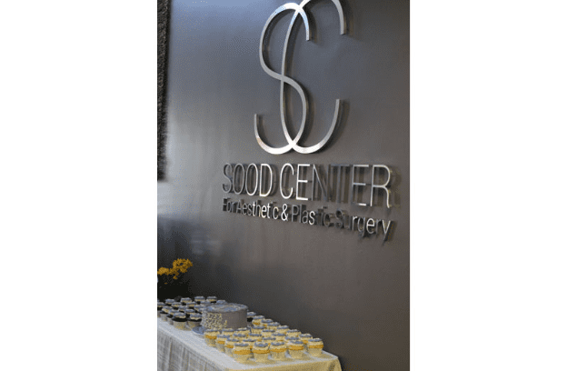 Cupcakes and Cake Set up Under the Sood Center Logo on the Wall